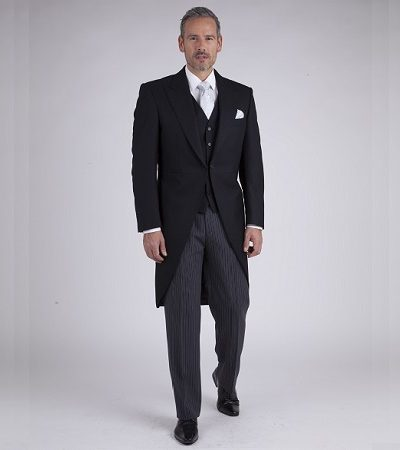 Man in black tail coat with cream waist coast and shirt with ivory accessories and dark grey trousers